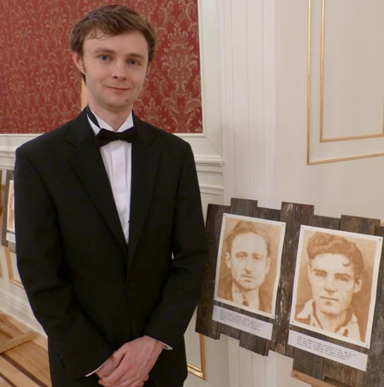 Jon England beside his line of portraits of the 50.