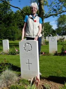Pat Rusciolelli stands at grave of her father's comrade-in-arms - A.A. Starfield - in Beny-sur-Mer cemetery.