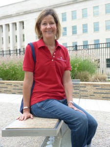 Laurie Laychak seated on the bench dedicated to her husband David Laychak, who was killed in the 9/11 attack on the Pentagon's southwest wall (pictured behind her).