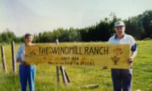 Noreen and Art Hawtin pose with the sign identifying their ranch est. 1936
