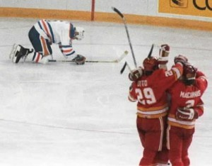 Calgary Flames celebrate a goal accidentally scored by Edmonton Oilers defence man Steve Smith (who's collapsed in background).