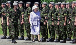 Queen Elizabeth doing what only Royalty can do well - reviewing the troops.