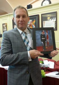 Joe Tilley hold photo of his son Spencer during his time in Canadian Forces.