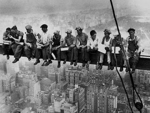 "1930 Lewis Hine photograph depicting ""skywalkers,"" steelworkers atop Empire State Building, is often used to symbolize ""precarious work."""